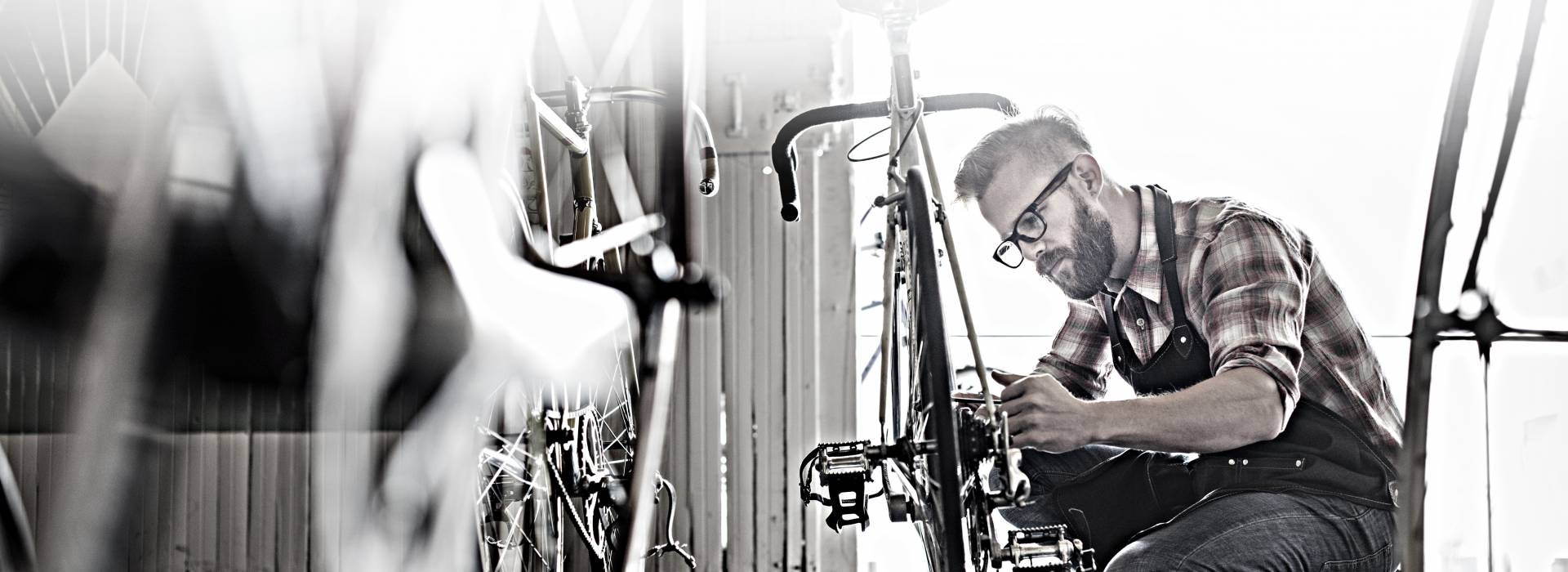 A small business owner fixes a bicycle in his bike shop.