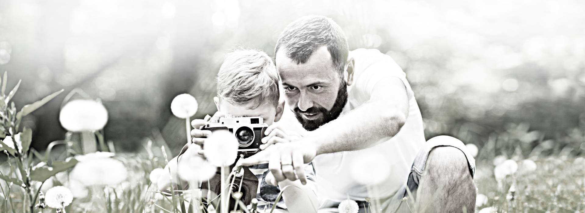 A father teaches his son how to use a camera.