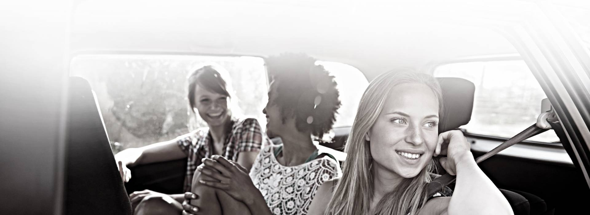 A woman sitting in the backseat of a car looks out a window while her friends cheerfully chat.
