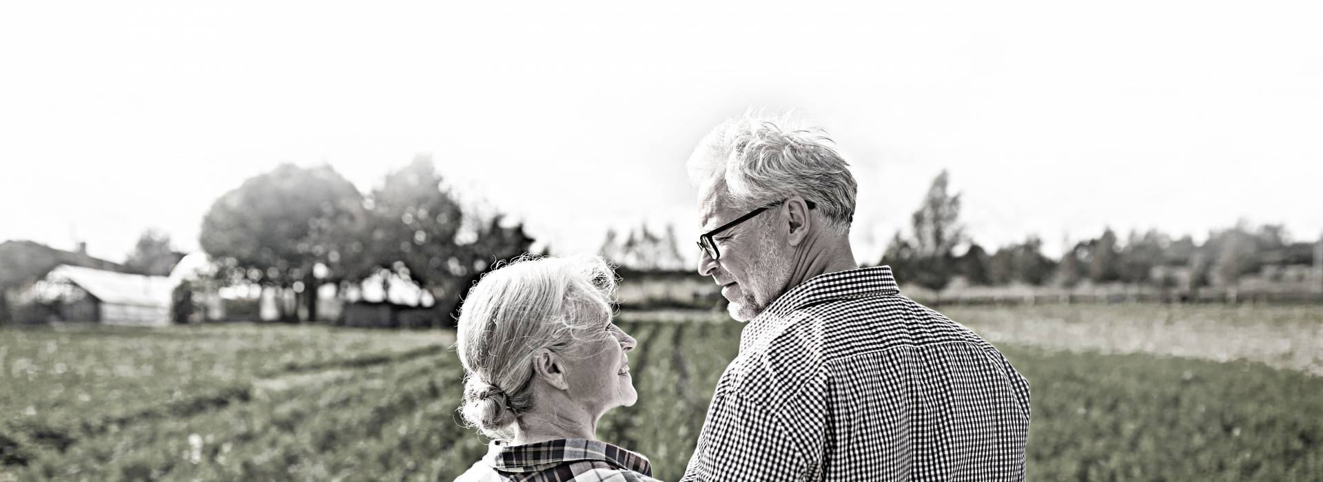 An elderly couple gaze into each others' eyes while standing in front of a field.