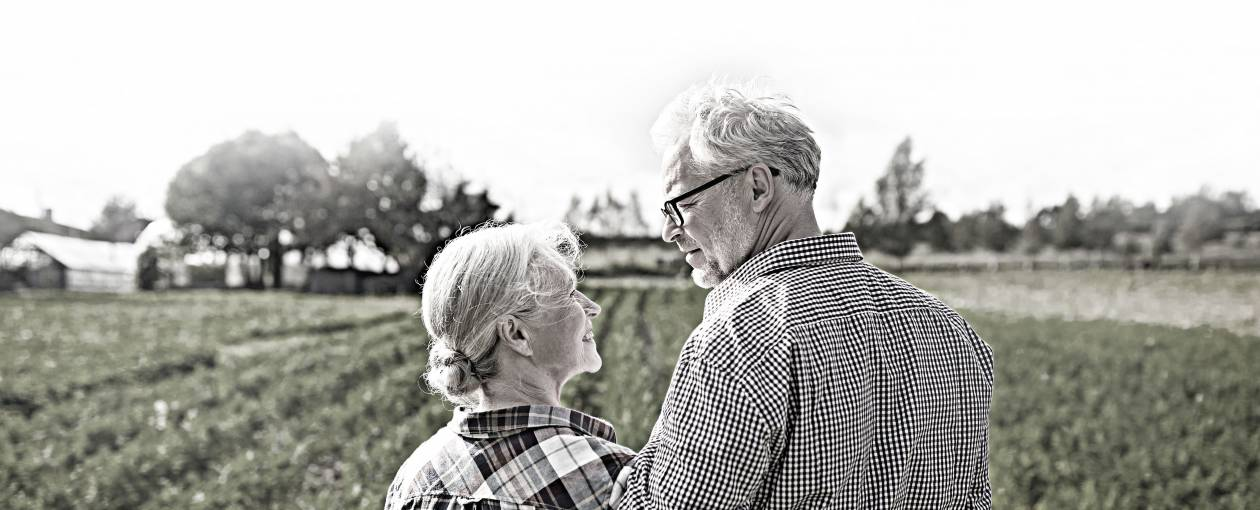 An husband and wife look into each others' eyes while standing in front of a field.