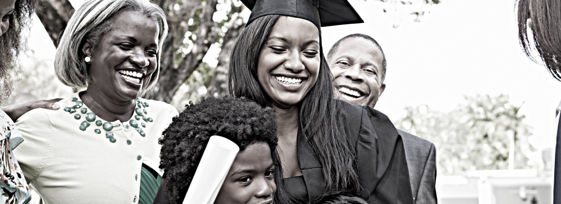 A woman who just graduated college hugs her children while her parents smile behind her.